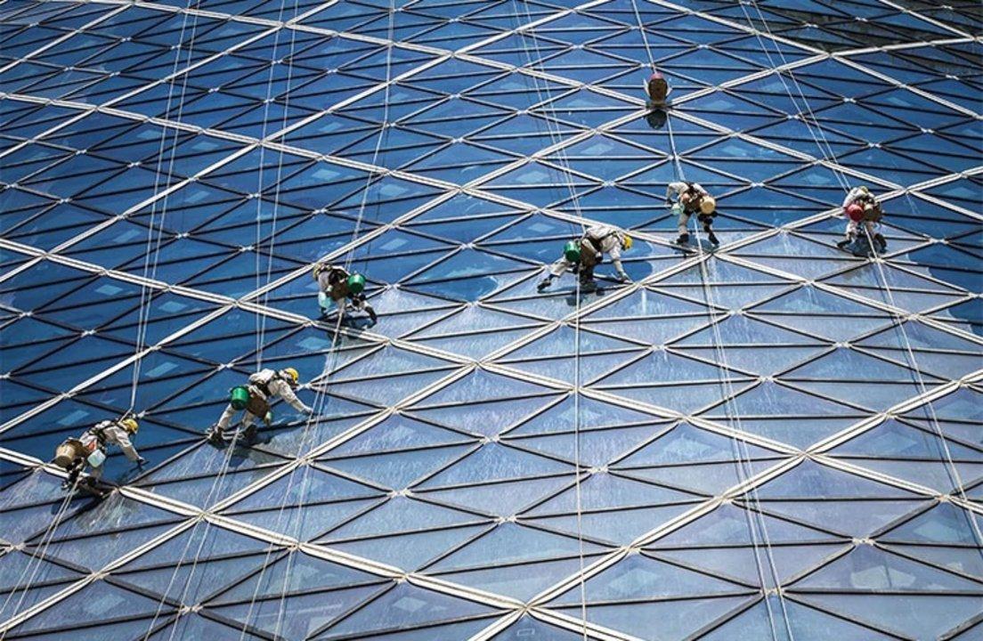 """Nombre: En el trabajo. Autor: Volker Sander. Descripción: """"Esta foto es el ejemplo de la necesidad de interacción entre humanos y los edificios. Sin el laborioso trabajo de las personas que limpian los gigantes marcos de vidrios de la torre, el vistoso rascacielos no luciría igual"""", según Sander."""